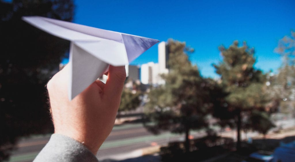 child with paper airplane